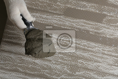 Worker holding adhesive mix on spatula above tile, closeup. Space for text