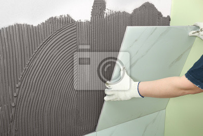 Worker installing ceramic tile on wall, closeup. Space for text