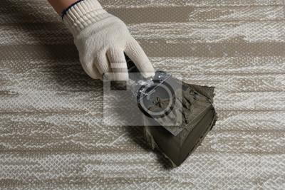 Worker spreading concrete on ceramic tile with spatula, closeup