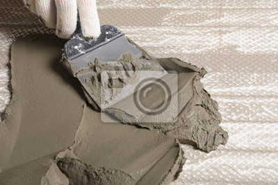 Worker spreading concrete on ceramic tile with spatula, closeup. Space for text