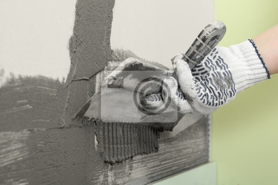 Worker spreading concrete on wall with spatula, closeup. Tile installation