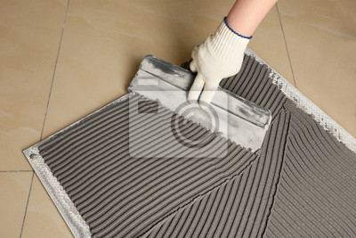 Worker spreading concrete over ceramic tile with spatula on floor, closeup. Space for text