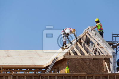 Naklejka Workers are working on the roof at construction