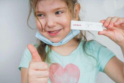 Naklejka Worldwide coronavirus epidemic concept. Pandemic COVID-19, 2019-nCoV. Kid girl with negative test strip for sars-cov-2 virus disease in hands. After Coronavirus recovery concept