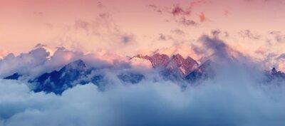 Naklejka Wysokie pasmo górskie w chmurach podczas wschodu słońca. Piękny krajobraz panoramiczny