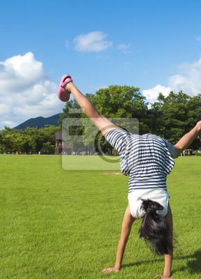 芝 生 広 場 で 側 転 の 練習 を す る 女 の 子