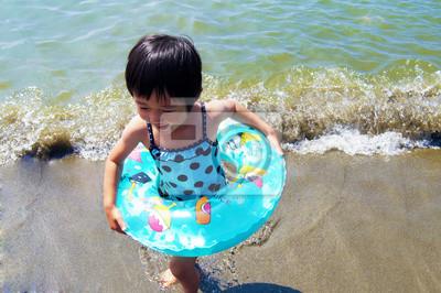 浮 き 輪 を 抱 え て 波 か ら 逃 げ る 少女