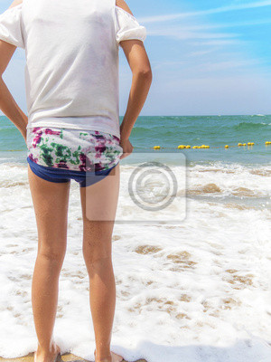 波 打 ち 際 で 海 を 見 て い る 女性