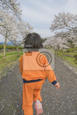 桜 並 木 の 中 を 走 る 子 供