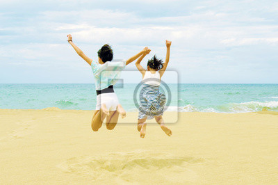 ビーチにて女の子同士で手を繋いでジャンプ