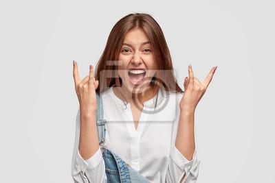 Naklejka Zadowolona, radosna młoda brunetka pokazuje rockowy gest, wiwatuje i celebruje coś, dzieli się pozytywnymi emocjami, zachwyca się fajną muzyką, trzyma szczęki upuszczone, krzyczy coś.