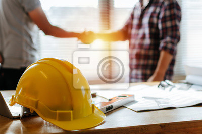 Naklejka yellow safety helmet on workplace desk with construction worker team hands shaking greeting start up plan new project contract in office center at construction site, partnership and contractor concept