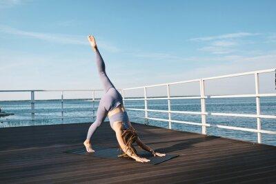 Naklejka Young active female bending forwards while keeping left leg raised during yoga exercise