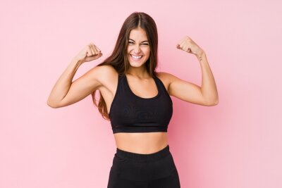Naklejka Young caucasian fitness woman doing sport isolated showing strength gesture with arms, symbol of feminine power