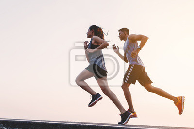 Naklejka young couple runner running on running road in city park