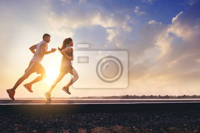 Naklejka Young couples running sprinting on road. Fit runner fitness runner during outdoor workout with sunset background