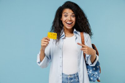 Naklejka Young fun african american girl teen student in denim clothes backpack point infdex finger on credit bank card isolated on blue background studio . Education in high school university college concept