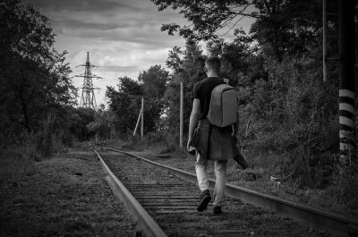 Naklejka young man in jeans with backpack on his back goes forward along abandoned railway. concept of frightening thing.