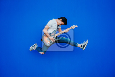 Naklejka young man jumping with electric guitar on blue background
