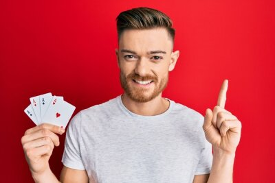 Naklejka Young redhead man holding ace poker cards smiling with an idea or question pointing finger with happy face, number one