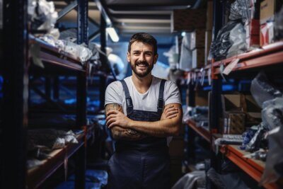 Naklejka Young smiling happy tattooed bearded worker in overalls standing in storage of import and export firm with arms crossed.
