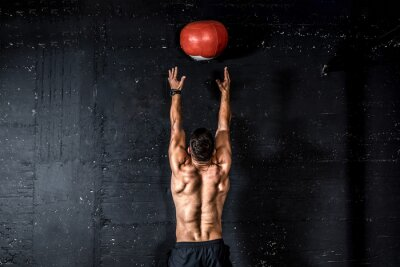 Naklejka Young strong sweaty focused fit muscular man with big muscles doing throwing medicine ball up on the wall for training hard core workout in the gym real people selective focus