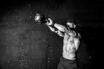 Naklejka Young strong sweaty focused fit muscular man with big muscles holding heavy kettle bell for swing cross training hard core workout in the gym black and white