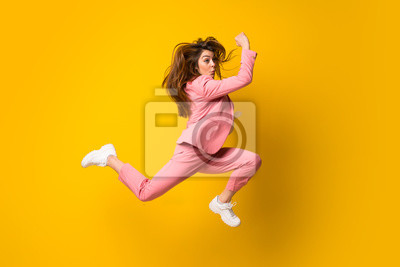 Naklejka Young woman jumping over isolated yellow wall