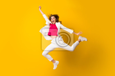 Naklejka Young woman jumping over isolated yellow wall making victory gesture