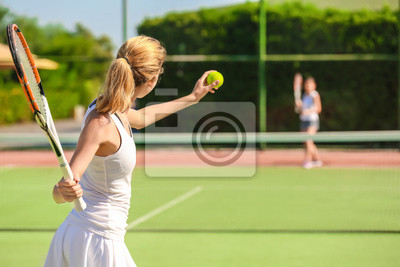 Naklejka Young woman playing tennis on court