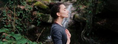 Naklejka Young woman practicing breathing yoga pranayama outdoors in moss forest on background of waterfall. Unity with nature concept.