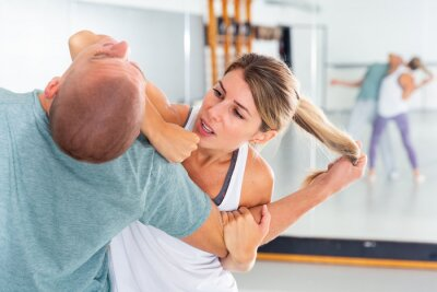 Naklejka Young woman practicing elbow blow with male partner during self defense course in gym..