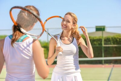 Young women playing tennis on court