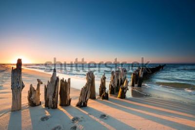 Naklejka Zachód słońca na plaży nad Morzem Bałtyckim i stary drewniany falochron