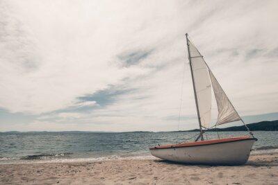 Naklejka Żaglowiec na tropikalnej plaży z niebieskim tle wody