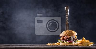 Naklejka Zakończenie hamburgeru domowy robić wołowina z nożem i dłoniakami na drewnianym stole
