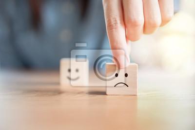 Naklejka Zakończenie up klient ręka wybiera smutną twarz i zamazaną smiley twarzy ikonę na drewnianym sześcianie, usługa ocena, satysfakci pojęcie.