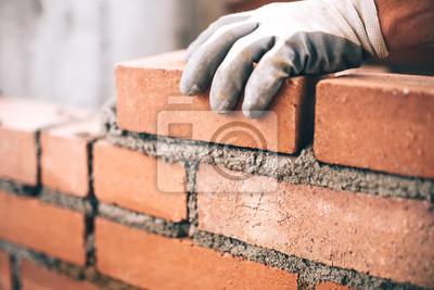 Naklejka Zamknąć murarza przemysłowego instalowanej cegły na budowie