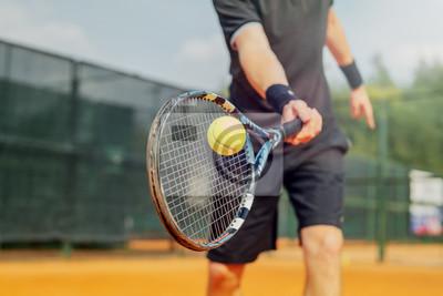 Naklejka Zamyka up mężczyzna bawić się tenisa i bije piłkę z rakietą.