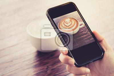 zdjęcie z filiżanką cappuccino z ciemnobrązowego drewna, podjęte przez telefon komórkowy