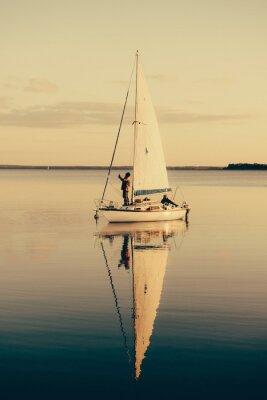 Naklejka Żeglowanie na spokojne jezioro z odbicia w wodzie. Serene krajobraz sceny.