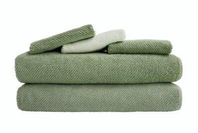 Zieleni kąpielowi ręczniki w stercie odizolowywającej nad bielem