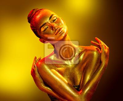 Złoty portret kobiety skóra zbliżenie. Seksowna wzorcowa dziewczyna z wakacyjnym złotym błyszczącym fachowym makeup. Złoty metaliczny korpus