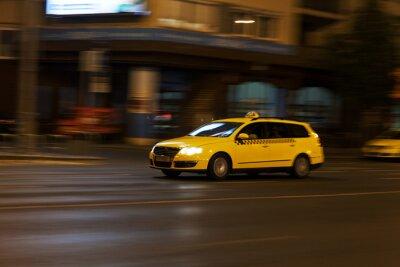 Naklejka żółta taksówka porusza się na ulicy miasta nocy