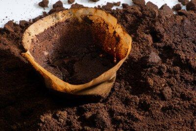 Naklejka zużyty papierowy filtr do przygotowania kawy leży na fusach kawy