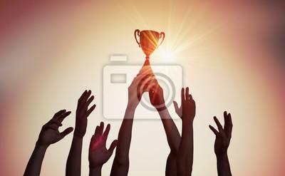 Naklejka Zwycięska drużyna trzyma trofeum w rękach. Sylwetki wiele ręki w zmierzchu.