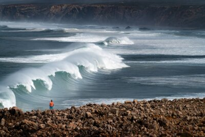 A surfer watching a set of waves breaking at the Bordeira Beach (Praia da Bordeira) in Algarve, Portugal