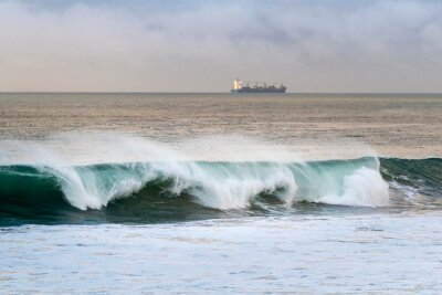A wave breaking at the Carcavelos Beach with a container ship on the background, in Portugal