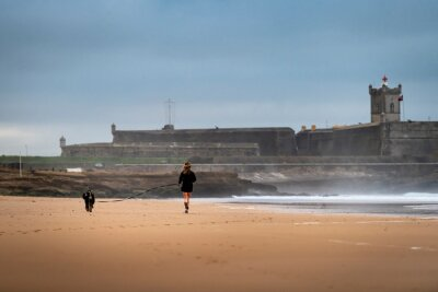 A woman running with her dog at the Carcavelos Beach in a winter morning, in Portugal.