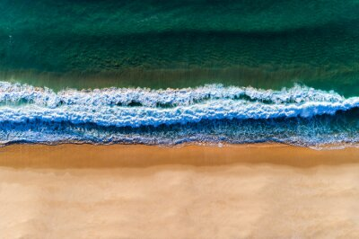 Aerial view of a wave breaking at the shore of the Comporta Beach in Portugal.